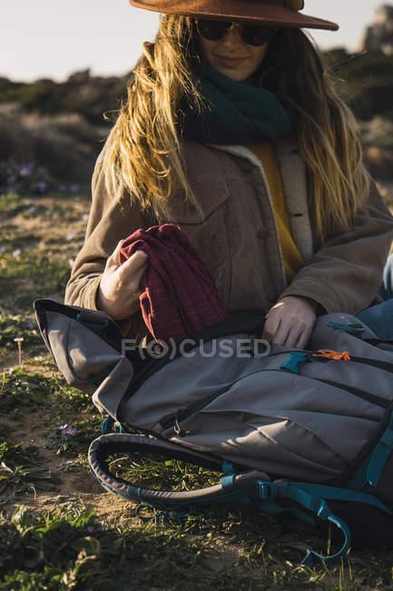 Italia, Cerdeña, mujer en un viaje de senderismo tomando un descanso tomando algo de la mochila - foto de stock