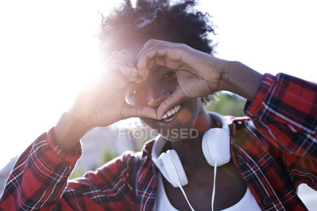 Retrato de una joven feliz dando forma a las manos a un corazón - foto de stock