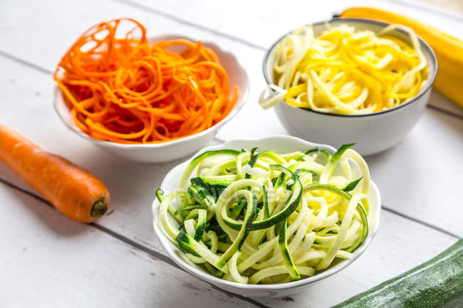 Zoodles, green and yellow zucchini, carrot on white wood — Fotografia de Stock