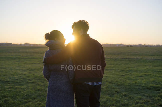 Young couple walking on meadow at sunset — Stock Photo