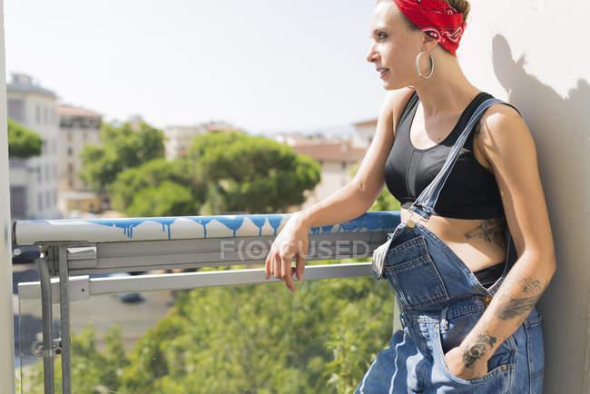 Joven tatuada de pie en el balcón mirando a la distancia - foto de stock