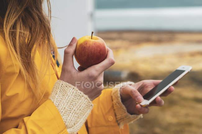 Ісландія, крупним планом Жінка тримає стільниковий телефон і яблуко — стокове фото