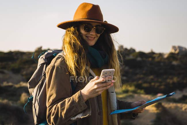 Italien, Sardinien, lächelnde Frau auf einer Wanderung mit Handy und Karte — Stockfoto