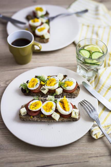 Вегетаріанський сніданок з хлібом, яйцями, томатними скибочками на тарілку і каву — стокове фото
