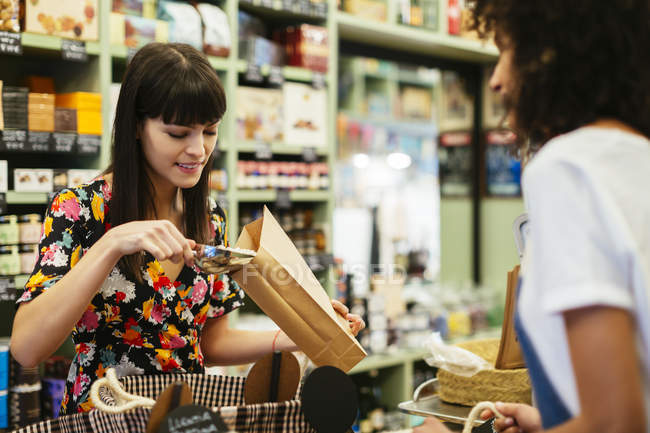 Smiling customer filling paper bag at counter of a store — Stock Photo