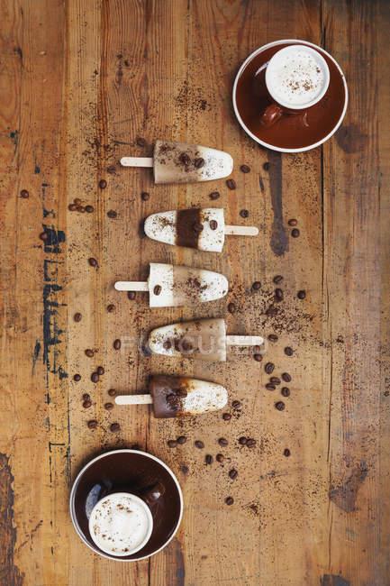 Домашний эспрессо Macchiato и латте Macchiato ледяные ледяные леденцы с кофейными зернами на деревянном фоне — стоковое фото
