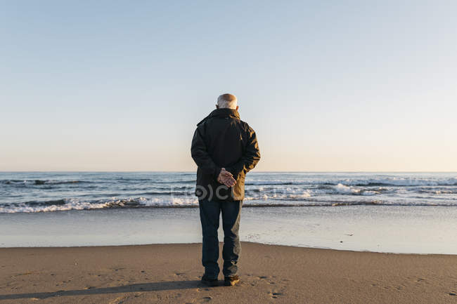 Senior man standing on beach and  keeping hands behind back — Stock Photo