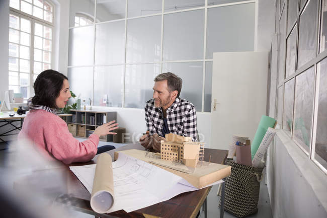 Colleagues discussing architectural model in office — Stock Photo