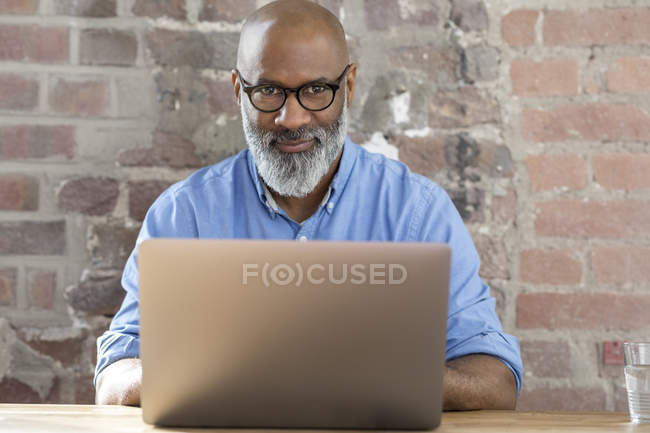 Portrait of smiling african american businessman using laptop — Stock Photo