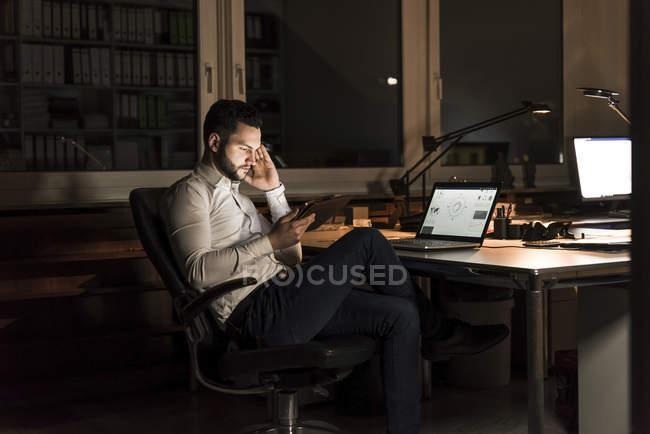 Homme d'affaires utilisant une tablette au bureau la nuit — Photo de stock