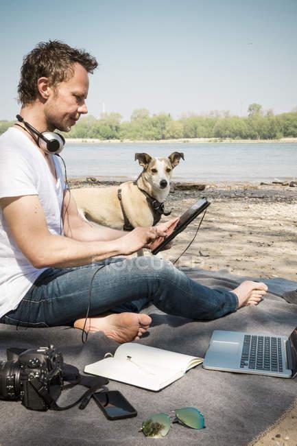 Людина з собакою сидить на ковдрі біля річки за допомогою таблетки. — стокове фото