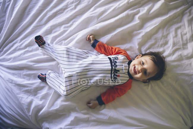 Retrato de menina sorrindo usando macacão deitado na cama — Fotografia de Stock