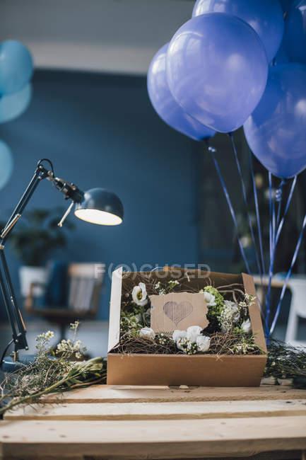 Disposizione floreale in una scatola sul tavolo — Foto stock