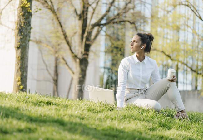 Giovane donna d'affari in pausa, utilizzando il computer portatile, seduto in erba e bere caffè — Foto stock