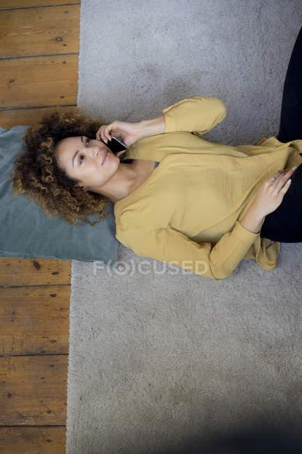 Mujer joven en el teléfono celular tumbada en el suelo en casa - foto de stock