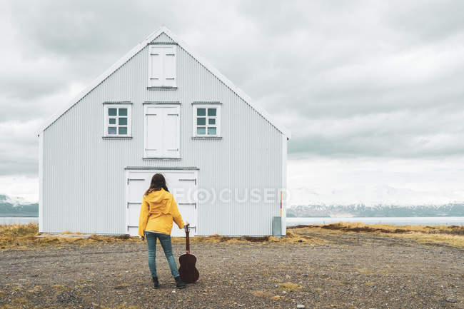 Iceland, woman with guitar standing at lonely house — Stock Photo