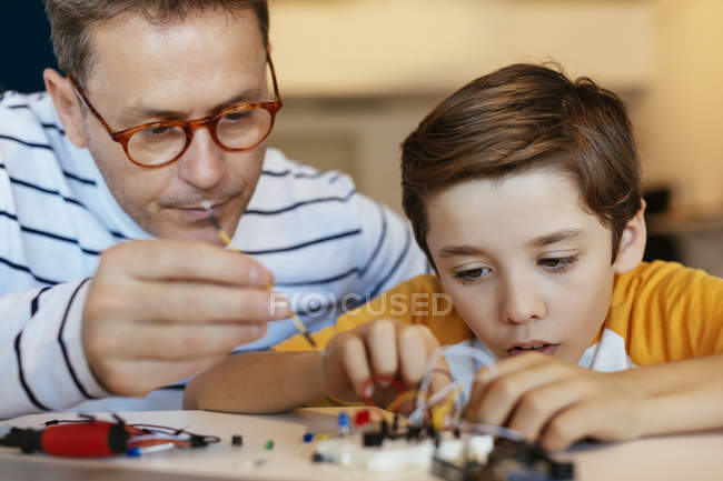 Father and son assembling a construction kit with laptop and wind turbine model — Stock Photo