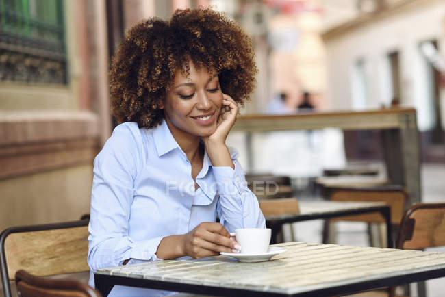Усміхнена жінка з афро зачіска сидить у відкритому кафе — стокове фото