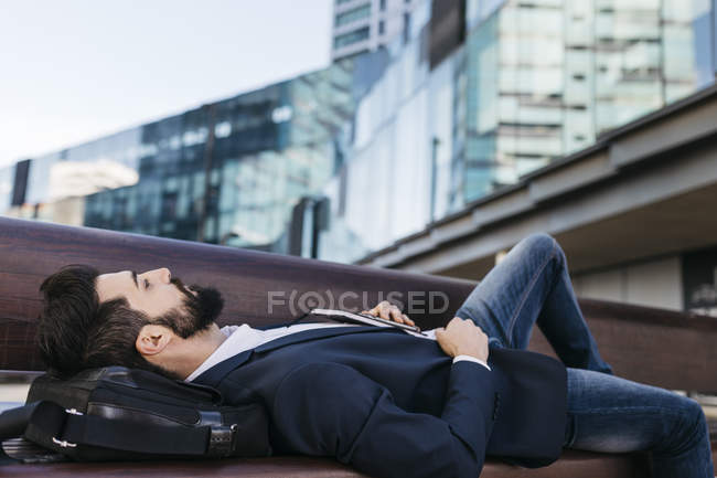 Businessman lying on bench outside office building — Stock Photo
