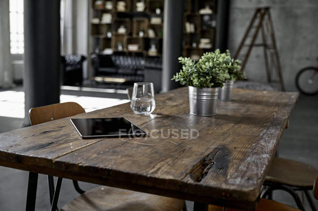 Tableta sobre mesa en loft plano - foto de stock