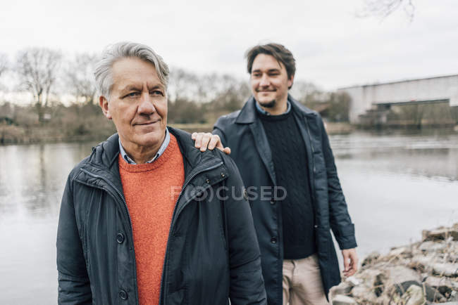 Confident senior man and young man standing at the riverside — Stock Photo