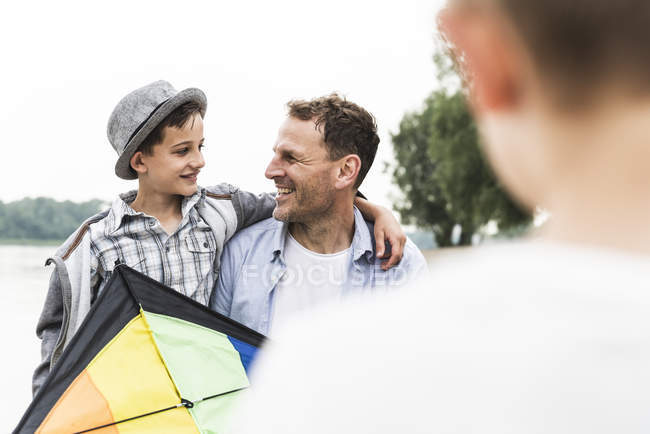 Happy father with two sons and kite outdoors — Stock Photo