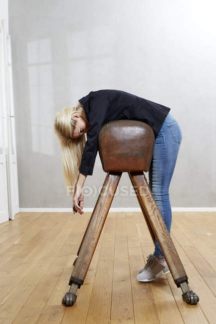 Woman leaning on pommel horse — Stock Photo