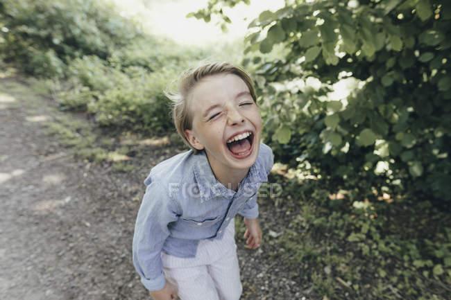 Garoto rindo no caminho da floresta — Fotografia de Stock