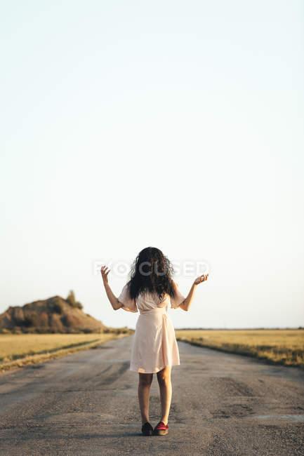 Молода жінка, що стоїть по дорозі, ховається за коричневим волоссям. — стокове фото
