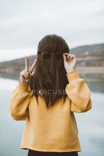 Drôle de 'portrait' de jeune femme avec des lunettes de soleil affichant le signe de victoire — Photo de stock