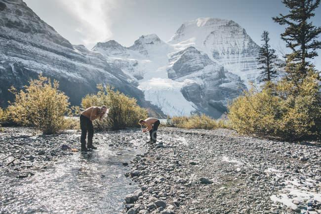 Канада, Британская Колумбия, Провинциальный парк Маунт Робсон, два человека, моющиеся в ручье — стоковое фото