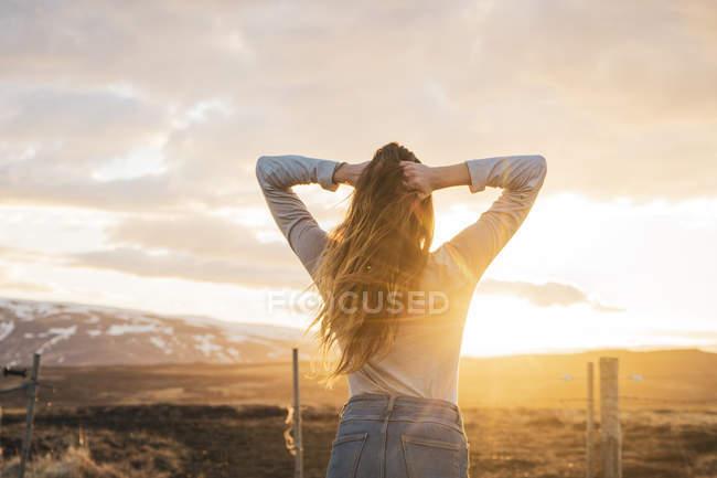 Islândia, jovem mulher com as mãos no cabelo ao pôr do sol — Fotografia de Stock