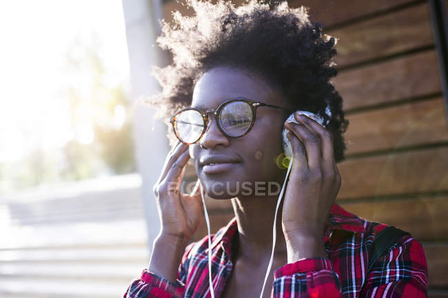 Portrait of smiling young woman listening music with headphones — Stock Photo