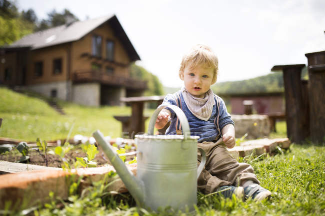 Boy in garden with watering can — Stock Photo