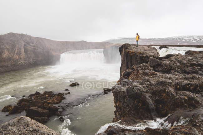 Iceland, woman standing at Godafoss waterfall — Stock Photo