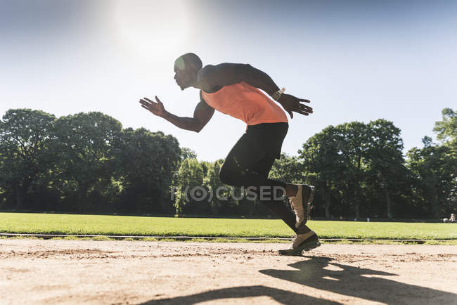 Young athlete on sports field training running — Stock Photo