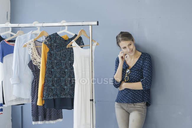 Портрет улыбающегося модельера в студии, прислоненного к стене — стоковое фото