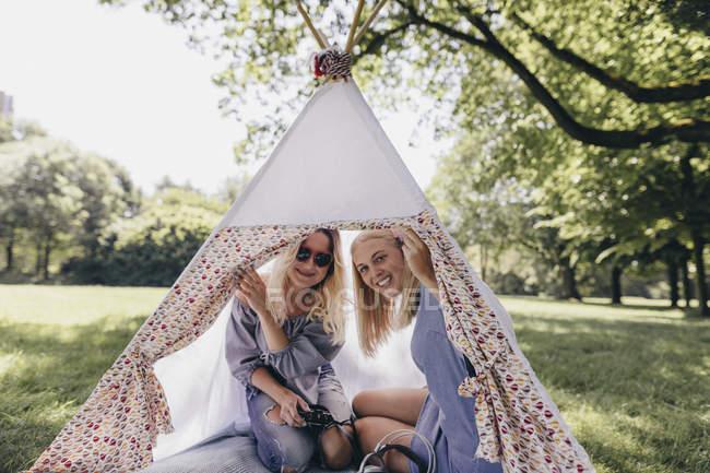 Дві щасливі молоді жінки з старомодною камерою в чайнику в парку. — стокове фото
