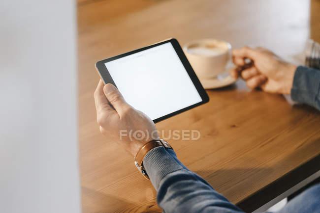 Gros plan d'un homme dans un café tenant une tablette — Photo de stock