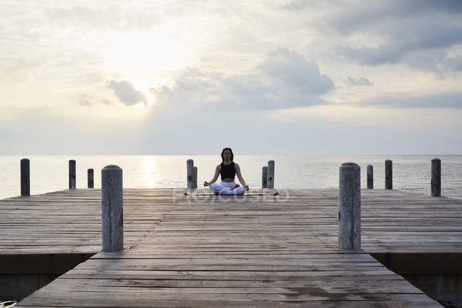 Young woman practicing yoga on a jetty by sea at sunset, meditating — Stock Photo