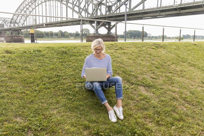 Старшая женщина, сидящая на дамбе с ноутбуком — стоковое фото