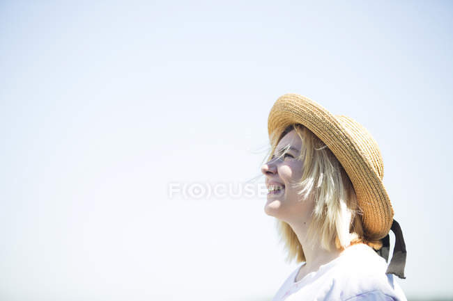 Young smiling woman with sun hat looking up, blue sky, copy space — Stock Photo
