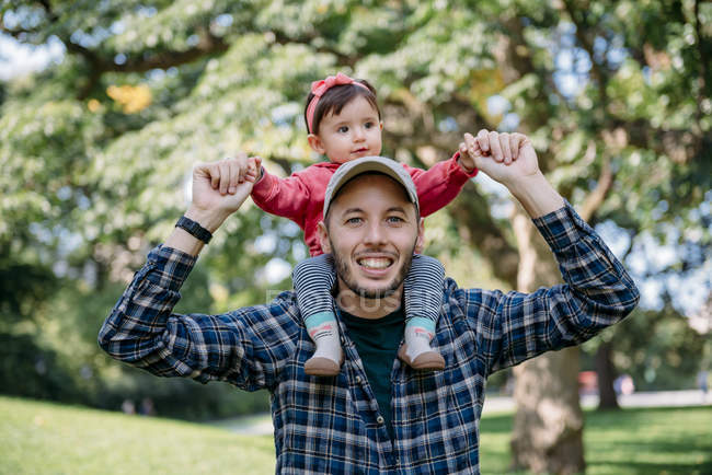 Соединенные Штаты Америки, New York, Father with baby girl on his shoulders walking through Central Park — стоковое фото