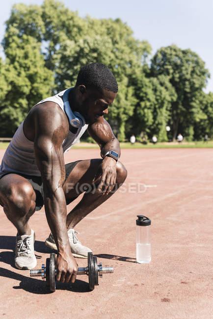 Юный спортсмен проводит силовые тренировки с гантелями на спортивной площадке — стоковое фото