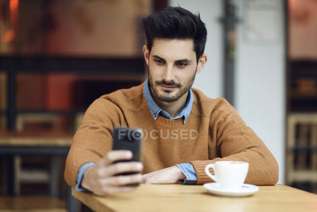 Portrait of young man sitting in a coffee shop using cell phone — Stock Photo