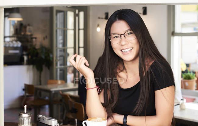 Asiatique jeune femme souriant à la caméra dans un café — Photo de stock