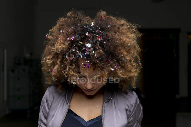 Жінка з конфетті у волоссі на чорному тлі. — стокове фото
