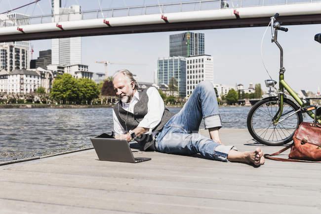Зріла людина з ноутбуком, навушниками і велосипедом лежачи на березі річки в місті — стокове фото