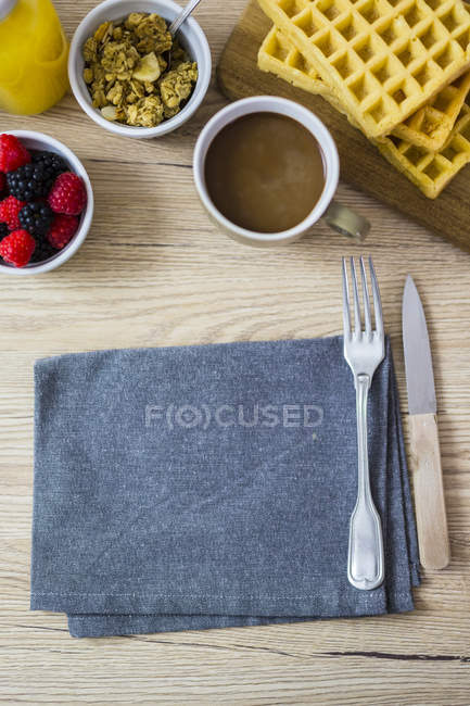 Breakfast table with waffles, wild berries and muesli — Stock Photo