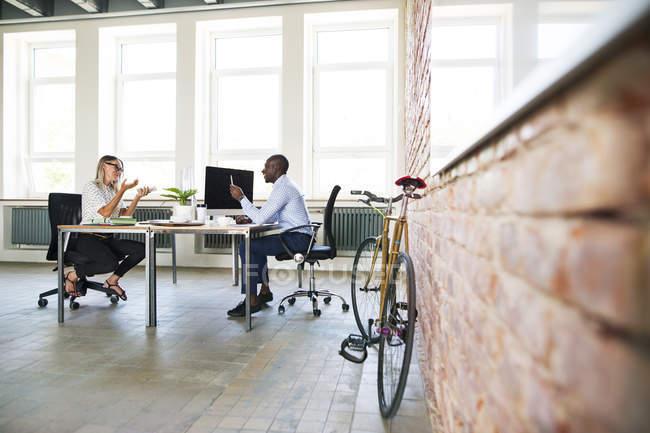 Коллеги по стартапу, сидящие в офисе, обсуждающие — стоковое фото